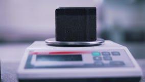 Mannen väger tegelsten i laboratoriumet arkivfilmer