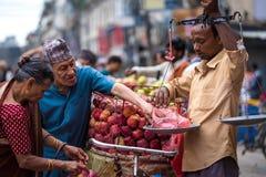 Mannen väger upp frukter på gatamarknaden i Katmandu, Nepal Fotografering för Bildbyråer