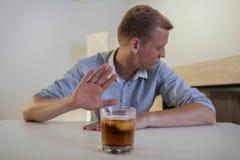 Mannen vägrar att dricka ett exponeringsglas av whisky Arkivfoton