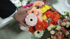Mannen väljer en blommatyp för blommabuketten för hans fru på blomsterhandeln