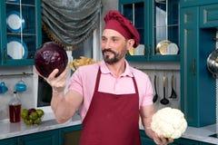 Mannen väljer grönsaker för att laga mat Den lyckliga kocken gör valde mellan den nya röd kål och blomkålen för sallad Kål och ca royaltyfri fotografi