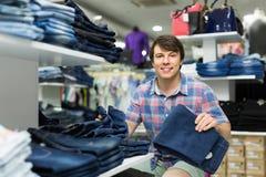 Mannen väljer jeans på klädlagret Royaltyfria Foton