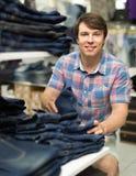 Mannen väljer jeans på klädlagret Arkivfoton