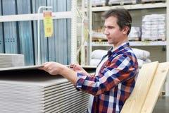 Mannen väljer och köper drywallen i lager Arkivfoto