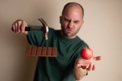 Mannen väljer upp en hammare för att slå en chokladstång med en hand och för att rymma ett äpple med annan, arkivfoto