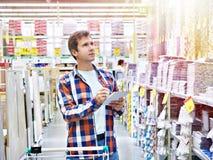 Mannen väljer väggtegelplattor för badrum i supermarketbyggnadskompis royaltyfri bild