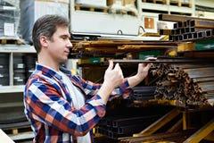 Mannen väljer vinkel och strukturellt stål för rebar i lager Arkivfoto