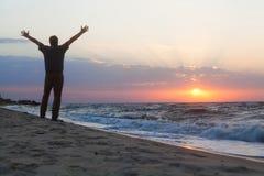 Mannen välkomnar soluppgången på stranden Royaltyfri Fotografi