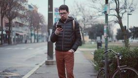 Mannen väntar bussen på station och använder smartphonen stock video