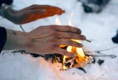 Mannen värme djupfrysta händer över en brand arkivfoton