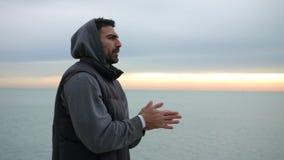 Mannen värmer hans händer upp, genom att andas på den kalla morgonsjösidan Morgonsoluppgång över havet arkivfilmer