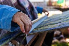 Mannen väver mycket utsmyckad mång- kulör ull genom att använda en trävävstol - 2/6 arkivbild