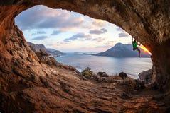 Mannen vaggar klättrareklättring längs ett tak i en grotta arkivfoto