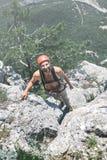 Mannen vaggar klättrareklättringar på klippan Royaltyfria Bilder