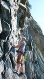 Mannen vaggar klättraren av en brant grad beskådar i början hans nästa flyttning royaltyfri fotografi