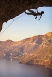 Mannen vaggar klättraren på den hängande över klippan royaltyfria foton