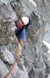 Mannen vaggar klättraren på en brant klättringrutt ser upp och ler arkivbilder