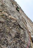 Mannen vaggar klättraren på en hård och brant klättringrutt i granitväggarna av Val Bregaglia i Schweiz royaltyfri foto