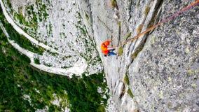 Mannen vaggar klättraren på en hård och brant klättringrutt i granitväggarna av Val Bregaglia i Schweiz arkivfoton