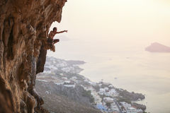 Mannen vaggar klättraren på solnedgången royaltyfria bilder