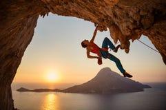Mannen vaggar klättraren som hänger med en hand på att utmana rutten på klippan arkivbild