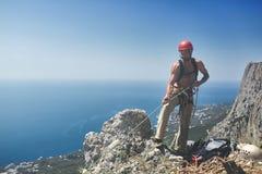 Mannen vaggar klättrareställningar på överkanten av klippan Royaltyfria Foton
