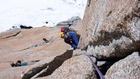 Mannen vaggar klättring som en brant vertikal granit vaggar klättringrutten i de franska fjällängarna nära Mont Blanc ovanför den arkivfoto