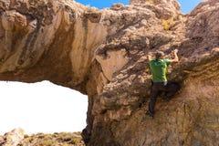Mannen vaggar klättringstenklippan, Salar de Uyuni Bolivia Arkivfoton