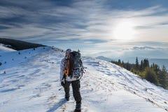Mannen vandrar i vinterberg arkivfoton