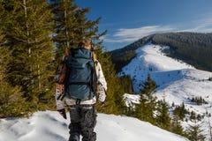 Mannen vandrar i vinterberg royaltyfria foton