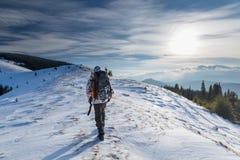Mannen vandrar i vinterberg arkivfoto
