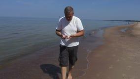 Mannen vid havsvisningen samlar skal lager videofilmer