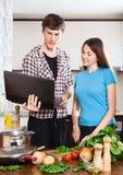 Mannen visar det nya receptet till flickan Arkivbild
