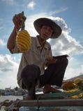 Mannen visar hans expertly skivade ananas arkivbilder