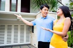 Mannen visar hans kvinna deras nya asiatiska hus Royaltyfria Bilder