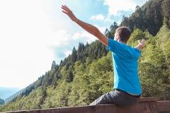 Mannens armar lyftte på en bro som korsar en flod som omgavs av berg arkivbild