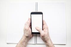 Mannens händer med den tomma smartphonen och dagboken, förlöjligar upp Royaltyfri Foto