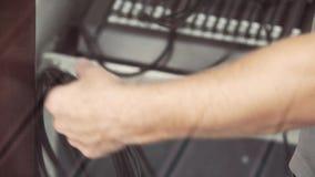 Mannens händer rymmer svarta kablar på oskarp bakgrund av elektroniskt material arkivfilmer