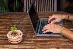 Mannens händer som arbetar för dator affärsplanet arkivbild