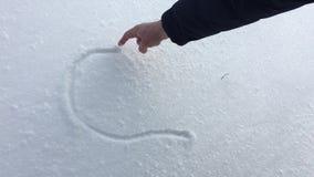 Mannens hand drar en hjärta i snön stock video