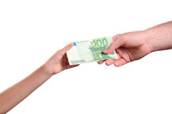 Mannens hand ger euroet för räkning 100 i ett barns hand Royaltyfri Foto