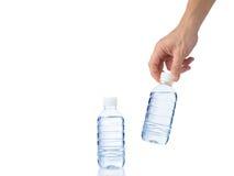 Mannens hand griper en flaska av vatten med en annan flaska av vatten Royaltyfri Foto
