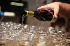 Mannens hand häller vin in i exponeringsglas royaltyfri foto