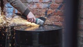 Mannens hand i brunt omslag använder det tunga elektriska snitt-avhjälpmedlet för att klippa burrell arkivfilmer