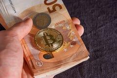 Mannens hand med bitcoin och 50 femtio euro av bakgrunder fakturerar sedlar Arkivbilder