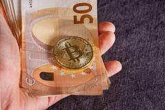 Mannens hand med bitcoin och 50 femtio euro av bakgrunder fakturerar sedlar Royaltyfri Fotografi