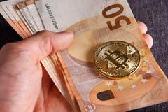 Mannens hand med bitcoin och 50 femtio euro av bakgrunder fakturerar sedlar Royaltyfria Bilder