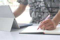 Mannens hand rymmer pennan på en tom anteckningsbok och en anteckningsbok royaltyfri fotografi