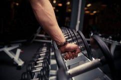 mannens hand tar en tung hantel i idrottshall Arkivbild