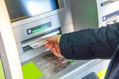 Mannens hand tar ut pengar från ATMEN royaltyfri foto